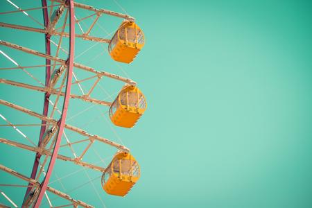 Yellow ferris wheel on blue sky - Vintage tone 免版税图像
