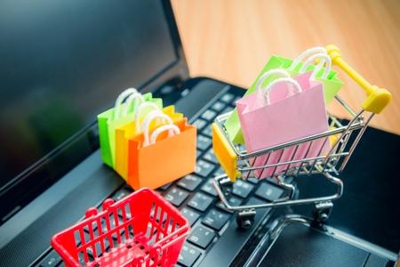 Modell bunte Einkaufstasche in Wagen und Korb auf Laptop. Einkaufen zu Hause oder Online-Internet-Shopping E-Commerce-Konzept Konzept. Weltweiter kommerzieller Service.