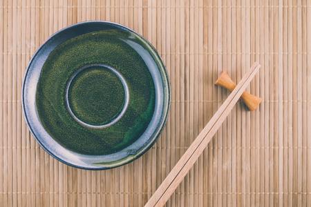 Flat lay handmade dish on Japanese mat background with sushi chopsticks