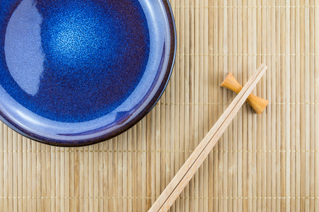 Flat lay handmade dish on Japanese mat background with sushi chopsticks