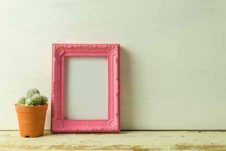 Vintage pink photo frame on old wooden table with cactus over white wooden background