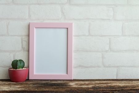 Pink photo frame on old wooden table with cactus over white brick wallpaper background