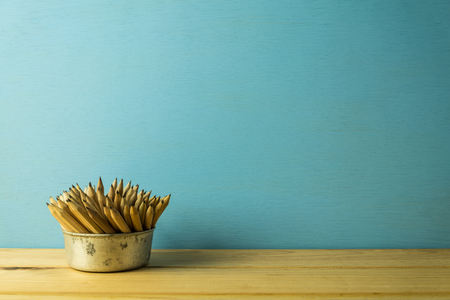 Many pencils on table over blue wooden background, back to school education concept