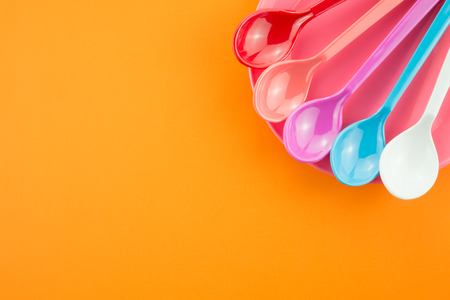 Colorful spoons and dish on orange background