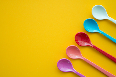 Colorful spoons and dish on yellow table Stock Photo
