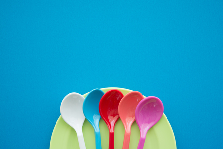 Colorful spoons and dish on blue background