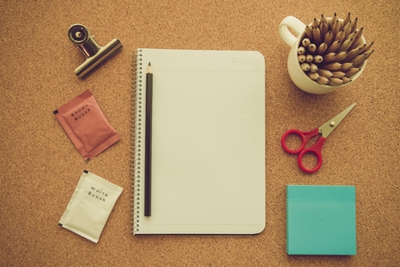 Blank notepad with office supplies and coffee cup on cork table. Top view - Retro filter effect