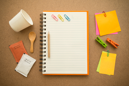 Above view of blank lined notepad with paper coffee cup and stationery on wooden table Standard-Bild