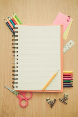Top view of education and business supplies on wooden table with empty space notepad - Retro filter effect 免版税图像