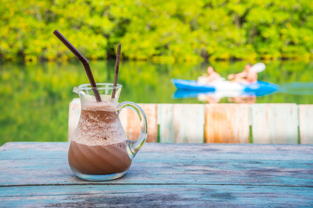 Iced chocolate smoothie on wooden table with warm beautiful lighting