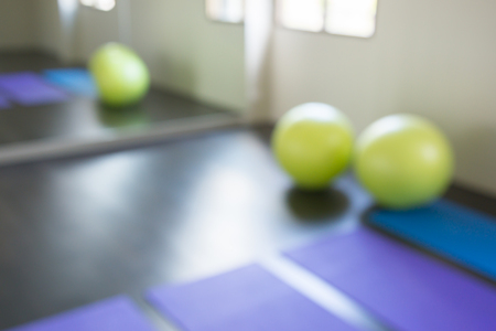 Abstract yoga balls and mat in fitness room background