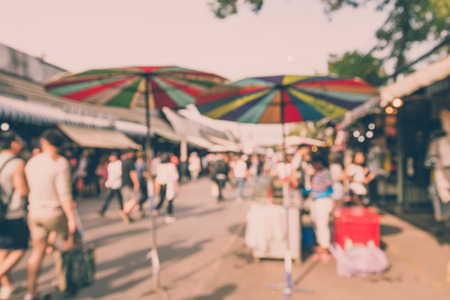 Abstract blur tourist shopping in Chatuchak weekend market outdoor in sunny day Bangkok Thailand background - Vintage filter effect