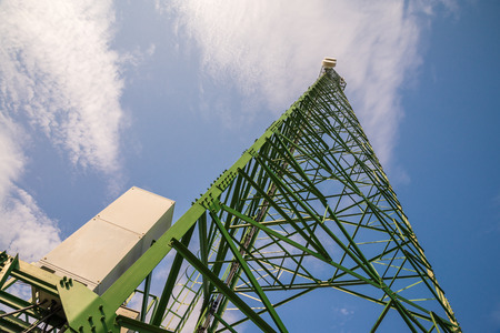 Green telecommunication tower against blue sky blue from bottom view