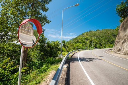 Up hill road turning on the mountains with outdoor traffic convex mirror, Thailand