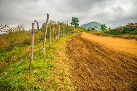Rural road on the mountain with cloudy