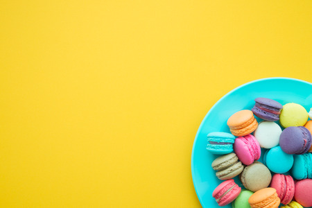 Colorful france macarons on yellow background Stock Photo