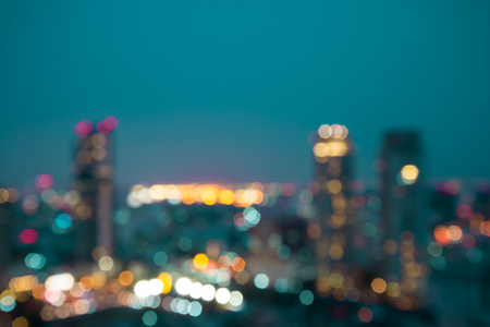 Defocused modern cityscape at night light background, blur urban skyscraper landscape twilight