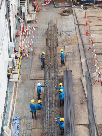 wokers work together to make stake of building by steel wire