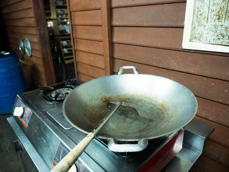 iron pan and turner after use on aluminum gas stove in wooden kitchen Banco de Imagens
