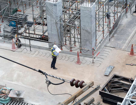 engineer with full safety set in construction area checking drawing