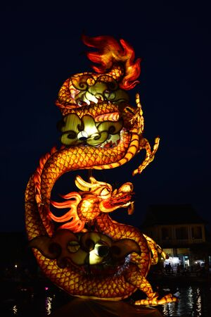 Luminous dragon figure at night at the harbor of Hoi An in Vietnam, Asia Stock Photo