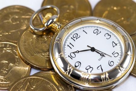 Golden watch around U S  coins  time is money concept