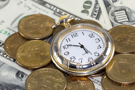 Golden watch around U S  coins  time is money concept