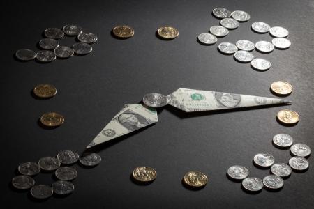 Klok gemaakt van Amerikaanse munten en dollars tijd is geld concept