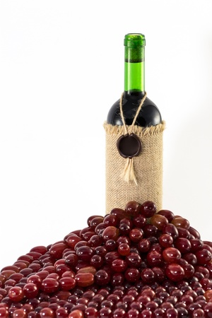 Red grapes around fabric-wrapped wine bottle