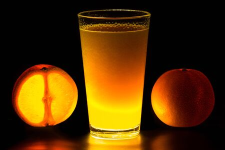 Close Up of glowing oranges and orange juice on black background Stock Photo