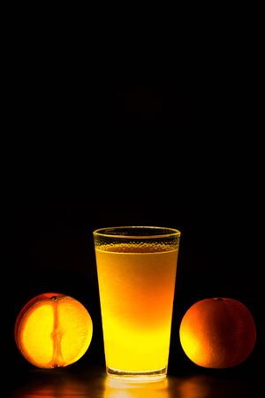 Close Up of glowing oranges and orange juice on black background Stock Photo