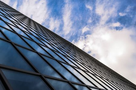 Angled view of a glass wall of an office building  Infinity effect in the blue sky  Stock Photo