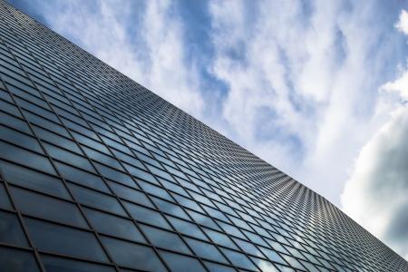 Schuin oog op een glazen wand van een kantoorgebouw Infinity effect in de blauwe hemel Stockfoto