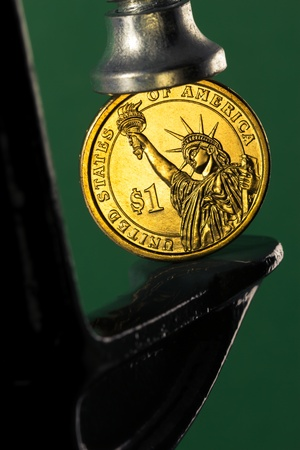 Pinching a golden dollar coin in a c clamp isolated on green background  financial pressure concept  Stock Photo