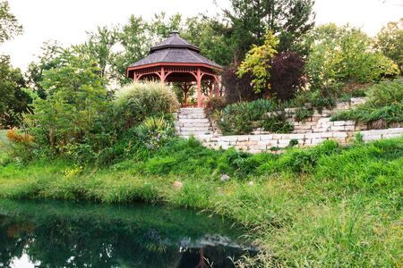 Secluded garden gazebo reflected in the water