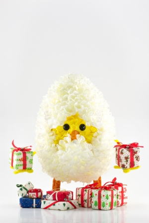 Isolated cute chick inside the egg holding gifts on white background