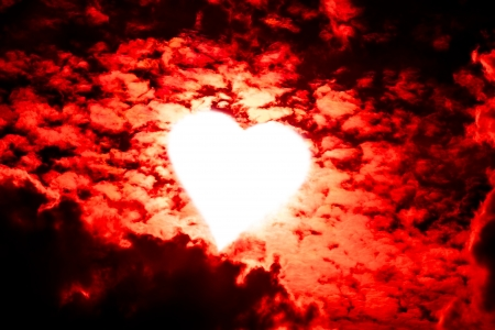 valentine background white shaped heart glowing through red clouds Stock Photo