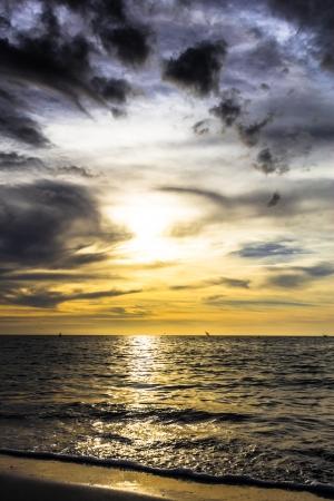 dramatische donkere bewolkte zonsondergang over de oceaan met vliegende meeuwen