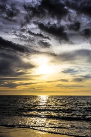 dramatische donkere bewolkte zonsondergang over de oceaan en het strand