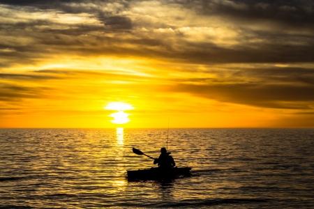 Visser in de kajak op de oceaan aan de voorkant van de spectaculaire zonsondergang