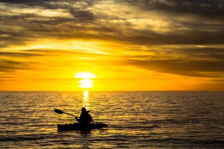 Visser in de kajak op de oceaan aan de voorkant van dramatische zonsondergang