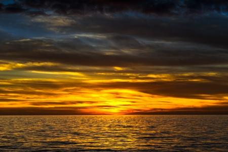 dramatische gouden zonsondergang over de oceaan Stockfoto