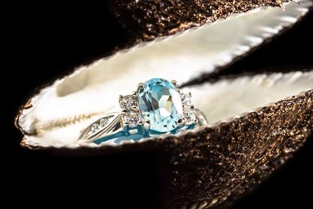 Ring met blauwe steen in een shell op zwarte achtergrond