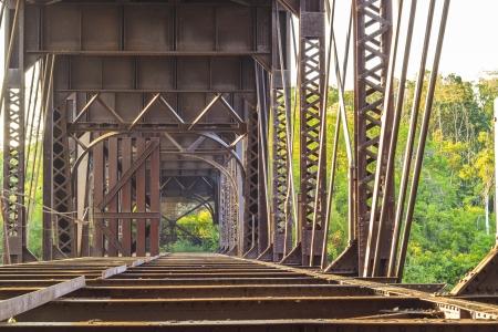 Oude roestige brug over de rivier