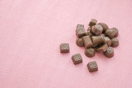 Chocolates set pile placed on pink background