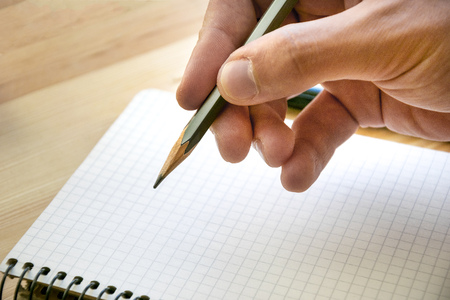 Pencil in male hand and clear sheet of notebook