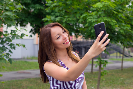 Happy brunette posing outdoors with telephone Stock Photo