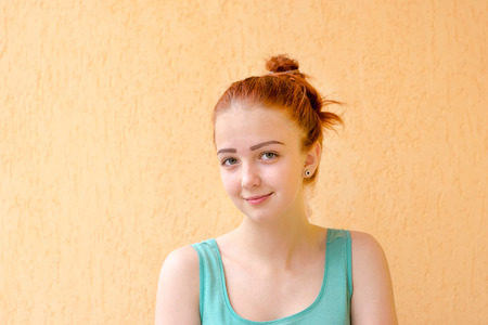 Close up shoot of young pretty lady without make-up with red hair tied in bun