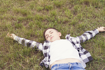 Joyful boy relaxing on green grass Stock fotó - 114555962