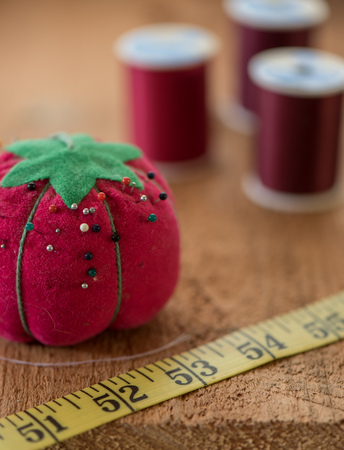 Sewing notions such as pincushion, tape measurer, and spools of thread sit on top of a rustic wood surface